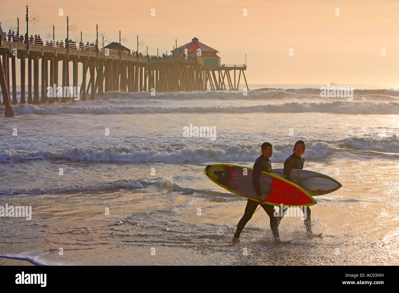 Surfers Walking Infront Of The Hunington Beach Pier Hunington Beach Orange County California United States MR Stock Photo