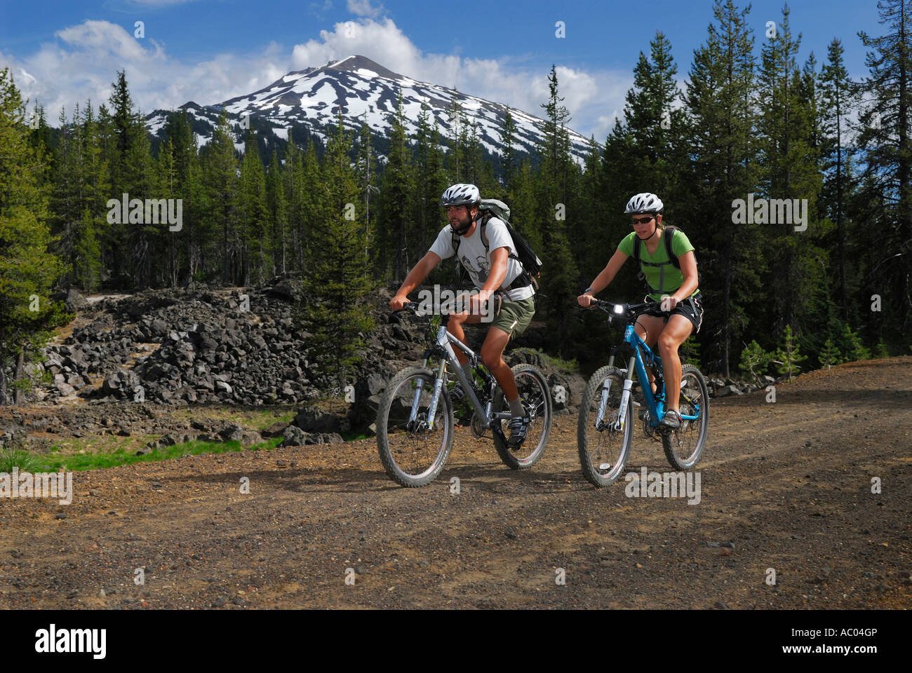 Mountain bikers in helmets traveling a dirt road under snow capped Mount Bachelor Oregon USA - Stock Image