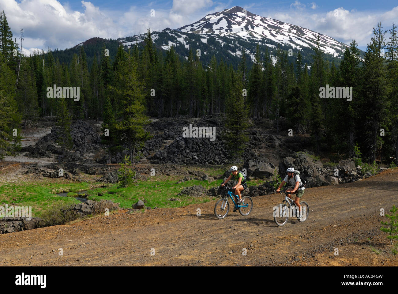 Mountain bikers riding along a dirt road under snow capped Mount Bachelor Oregon USA - Stock Image