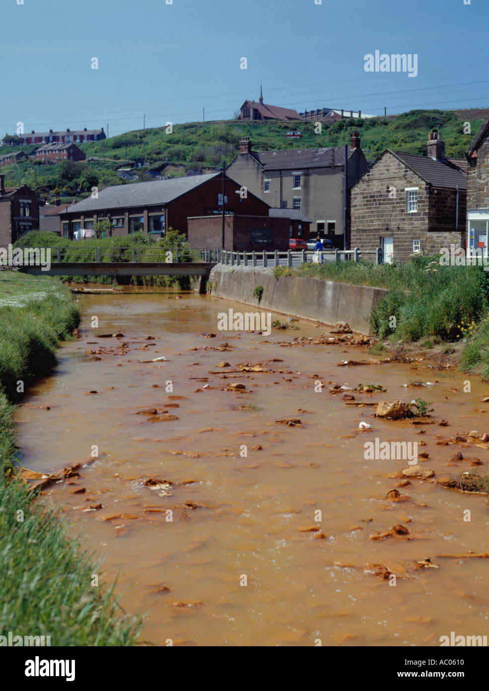 River pollution from iron oxide polluted ground water seeping from old ironstone mine, Skinningrove, Cleveland, England, UK. - Stock Image