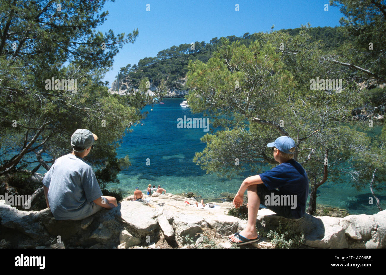 two boys looking out to sea over a picturesque cove port d allon