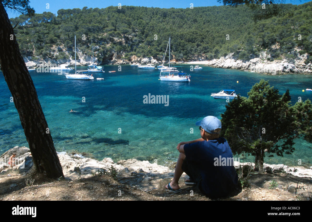 a boy looks out to sea over a picturequresque cove port d allon