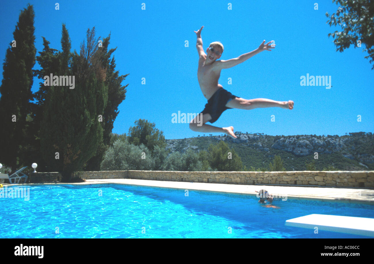 Teenage boy jumps for joy off diving board into villa swimming pool ...