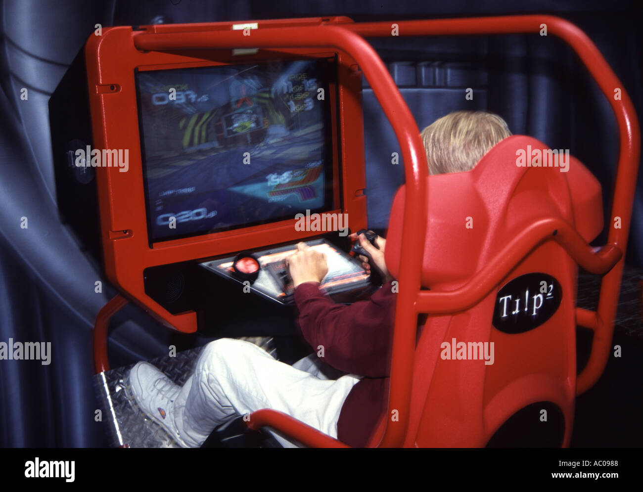Young boy playing a video arcade game - Stock Image