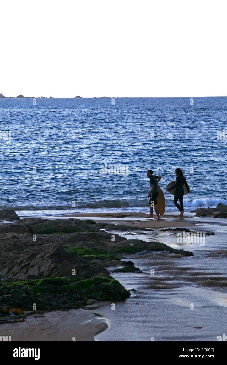 Surfers, Greve de Lecq beach, Jersey - Stock Image