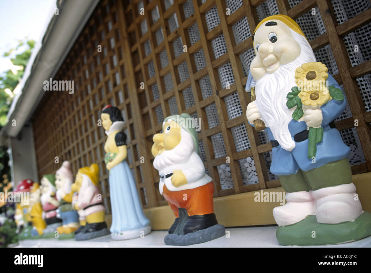 Little statues of Snow White and the seven dwarfs line the edge of a wall of a house in Grado, Italy. - Stock Image