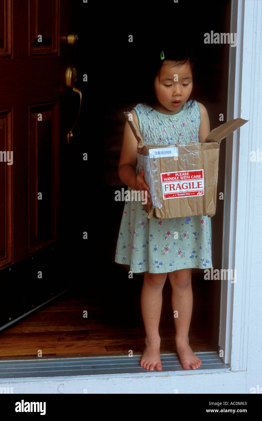 Girl opening fragile package from postal service - Stock Image