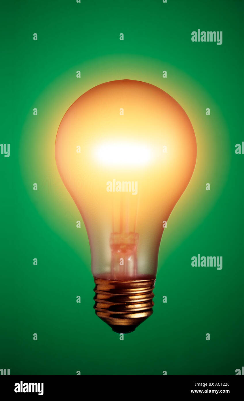 glowing light bulb on green background - Stock Image