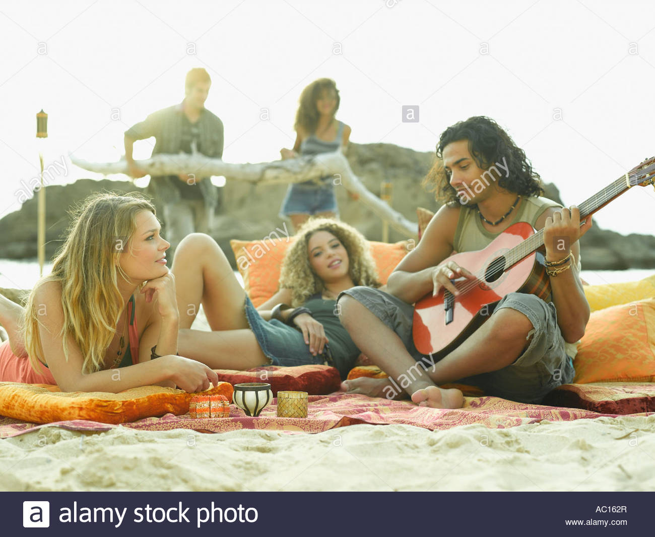 Young man playing the guitar with two young women lying beside him - Stock Image