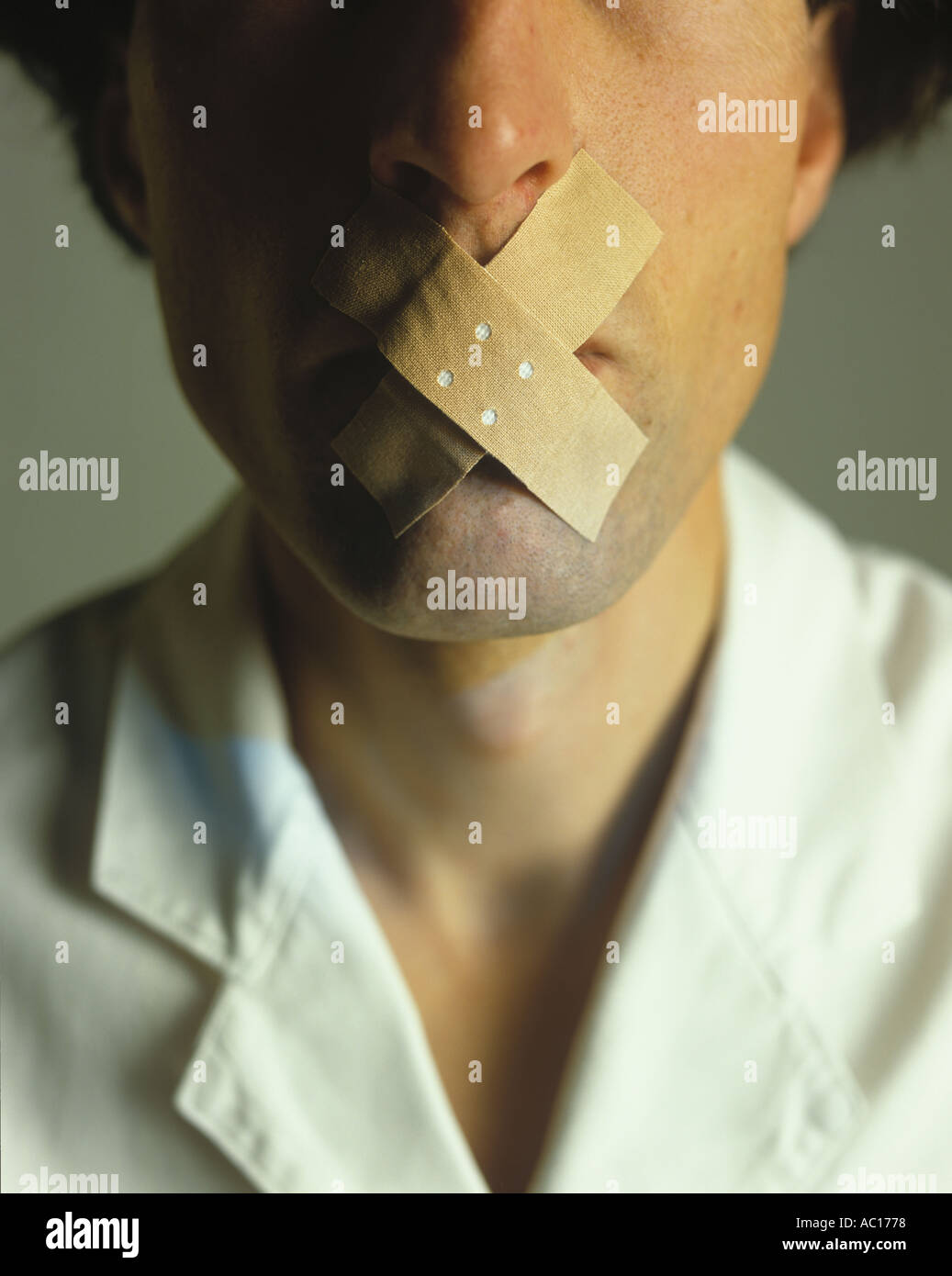 Mouth of a man taped with plaster Stock Photo