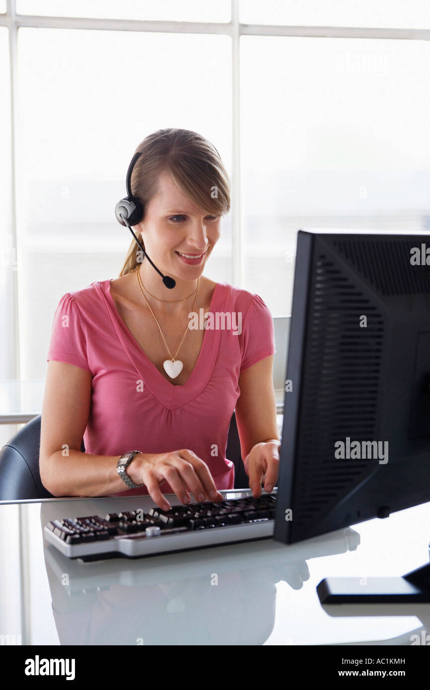 Woman working on computer, wearing headset - Stock Image