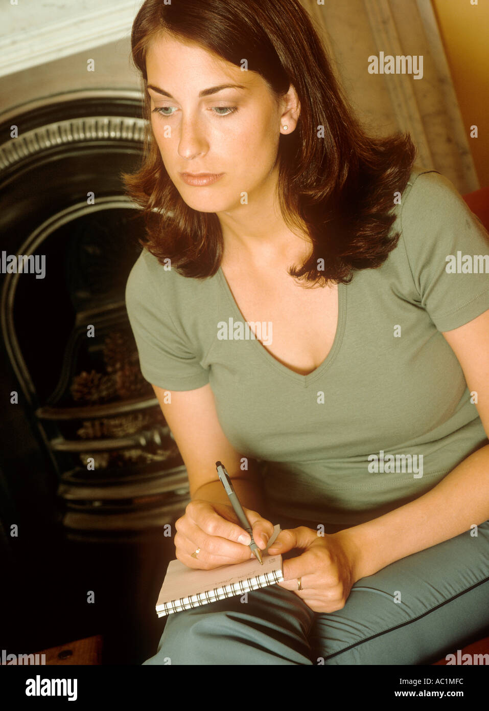 Woman sitting writing in a notebook Stock Photo