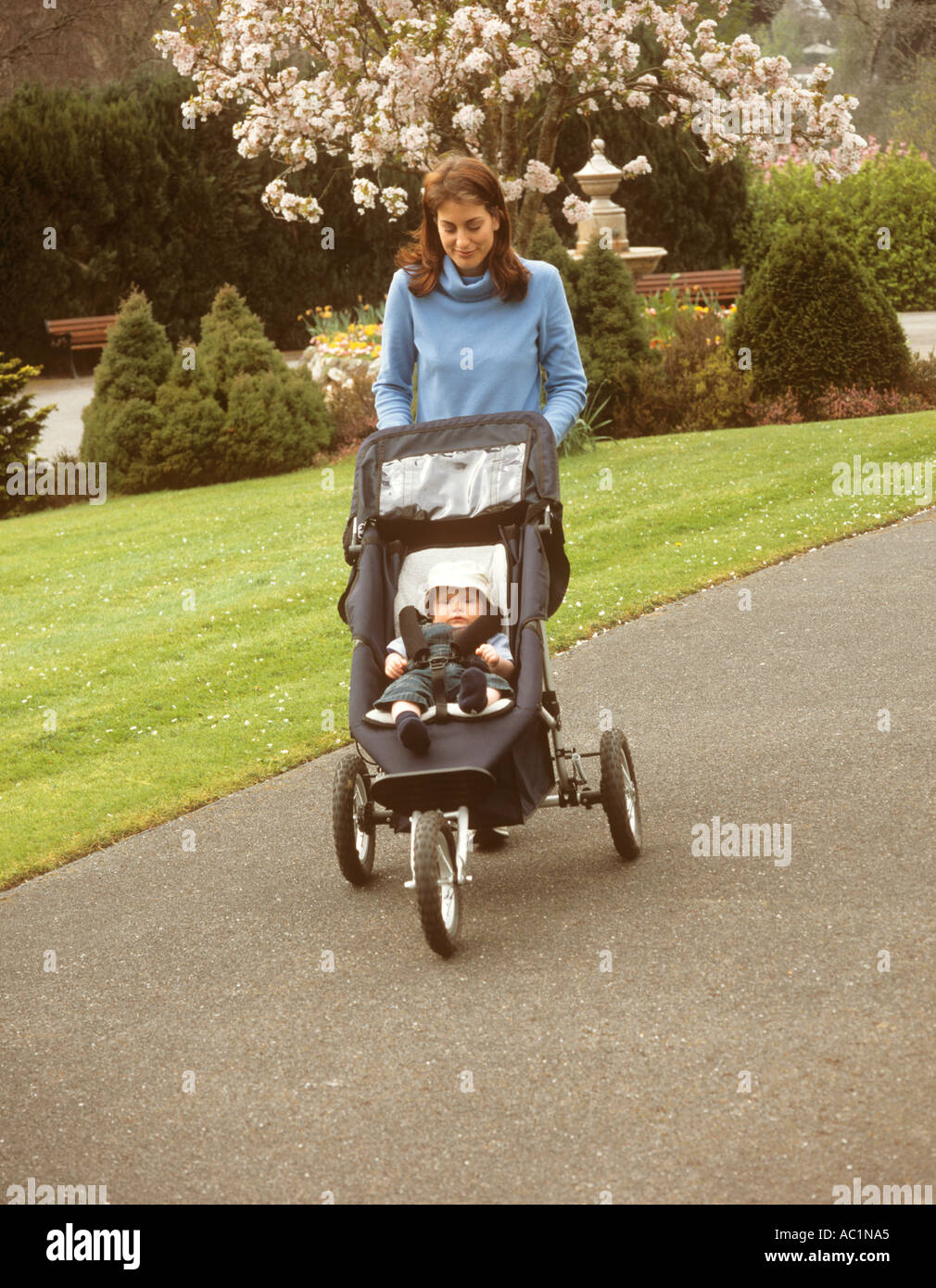 8eaf89a00308 Happy mother pushing her baby son in a pram in a park Stock Photo ...
