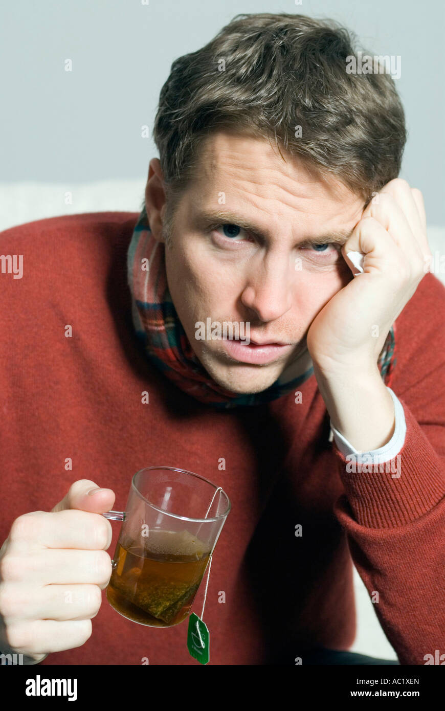 Man with cold a teacup in hands - Stock Image