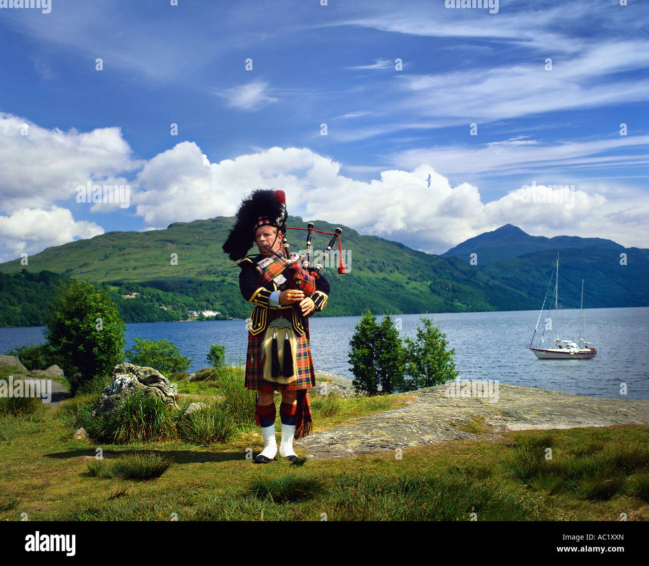 GB - SCOTLAND:  Scottish Piper at Loch Lomond - Stock Image