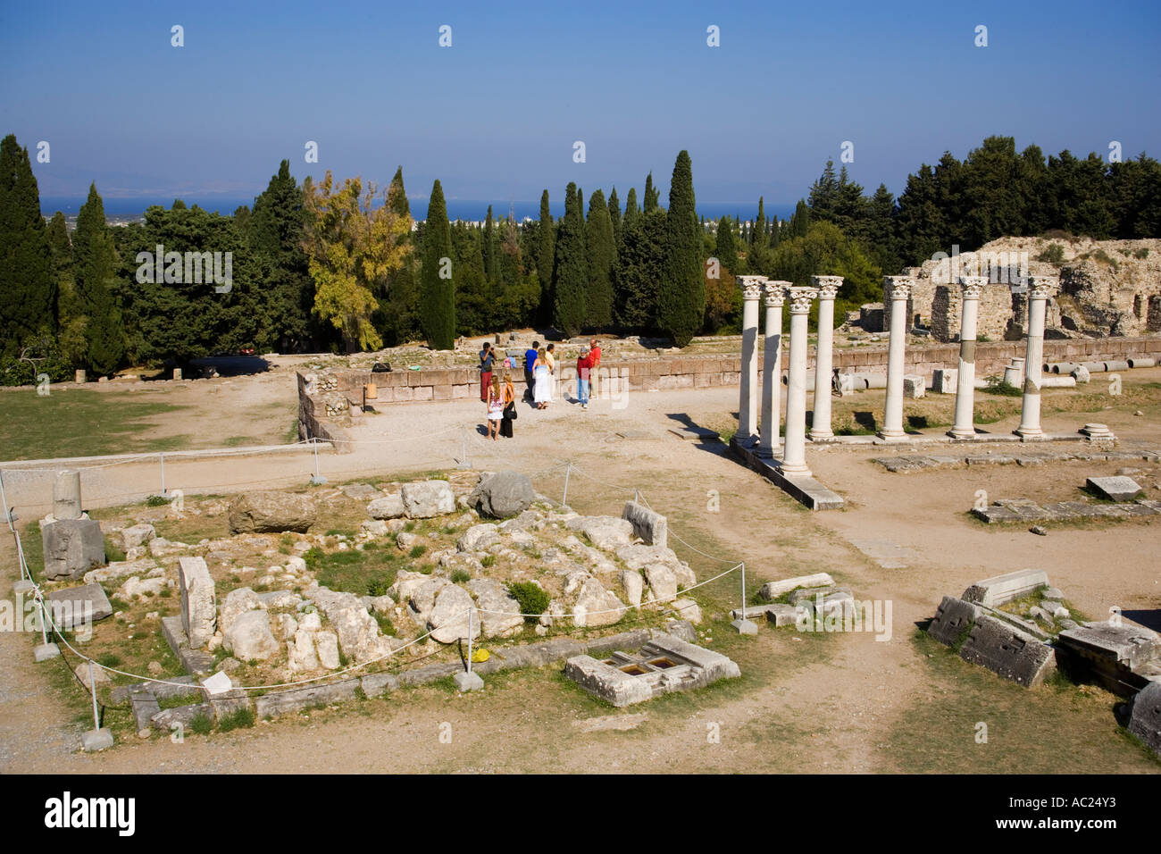 View to Altar of Asclepius and group of tourists in background at temple Asklipieion Kos Town Kos Greece Stock Photo