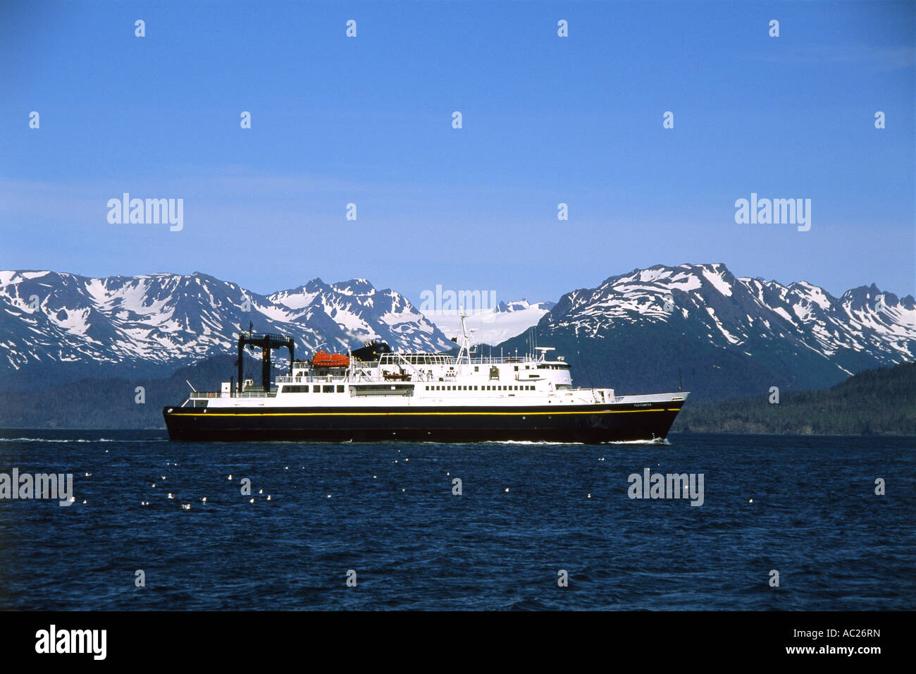 Ocean liner in body of water by mountains - Stock Image