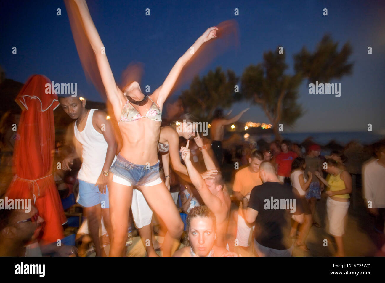 Young girl dancing by the full moon party of theTropicana Club Paradise Beach Mykonos Greece - Stock Image