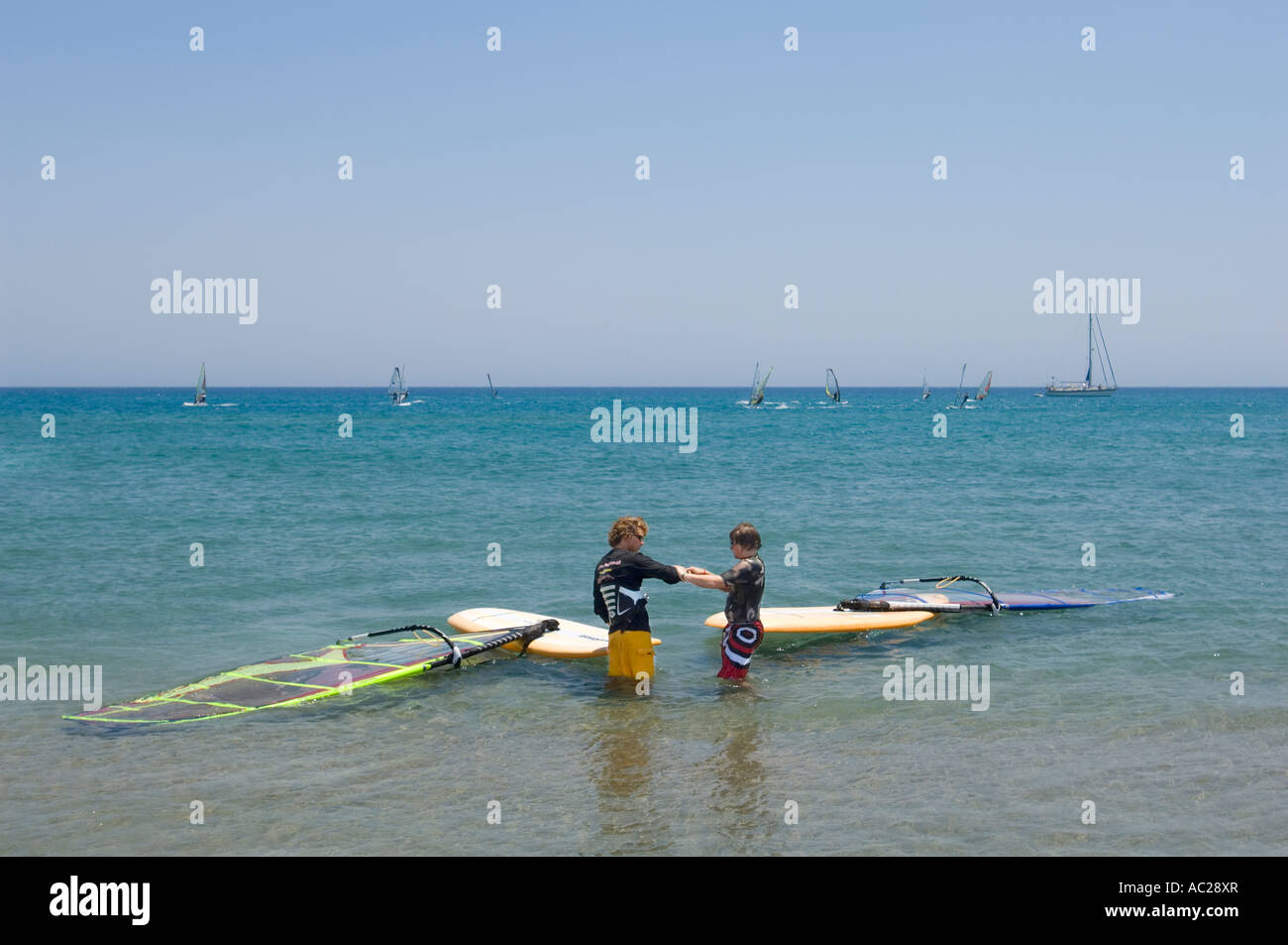A windsurfing instuctor teaching a student the basic skills of the sport with windsurfers in the background. - Stock Image