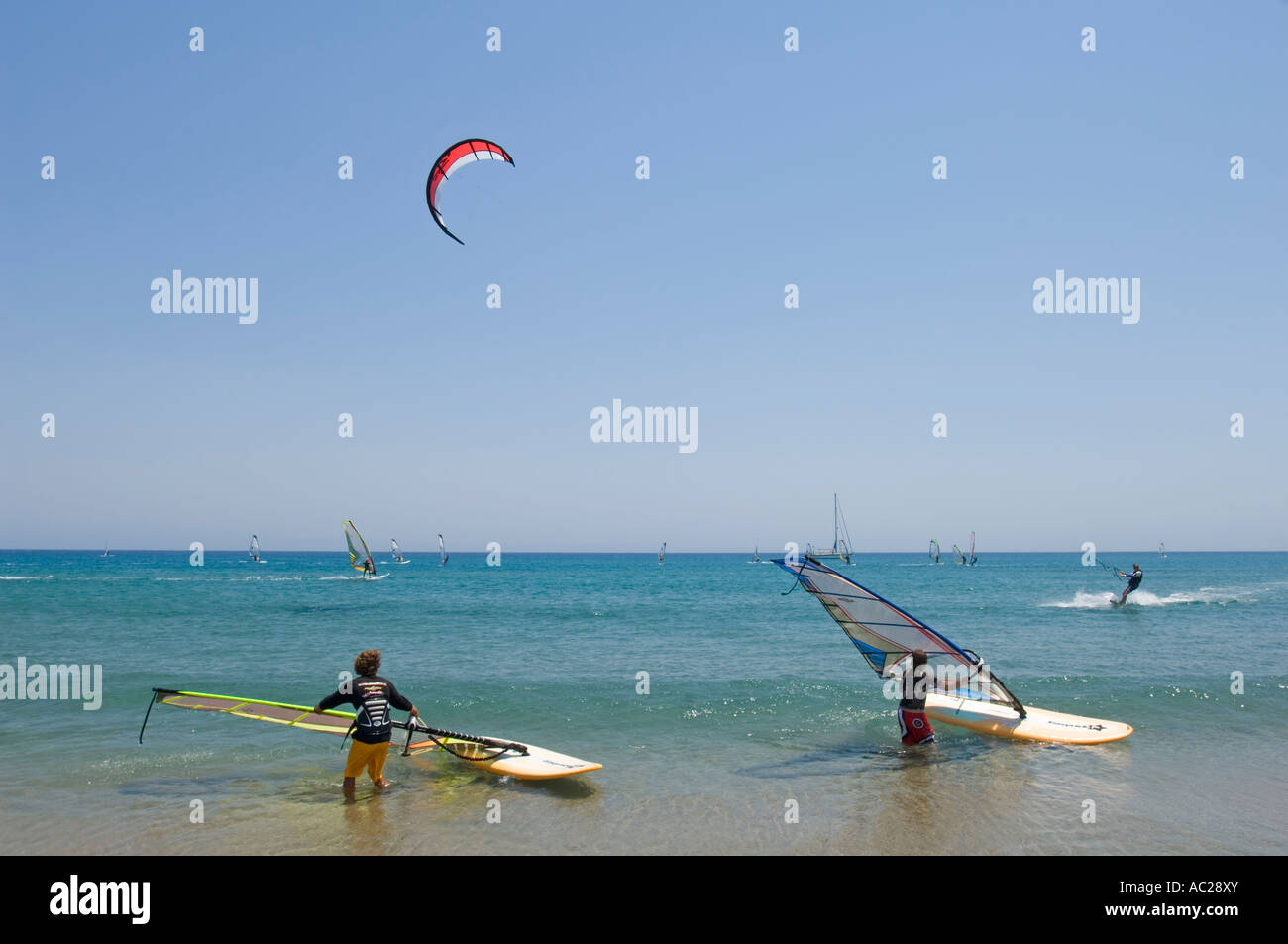 A windsurfing instuctor teaching a student the basic skills of the sport with windsurfers and a kitesurfer in the - Stock Image