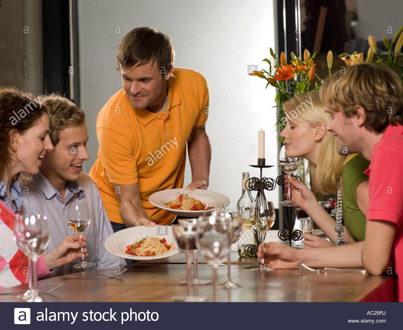 Young man serving noodles to two young couples at the dining table - Stock Image