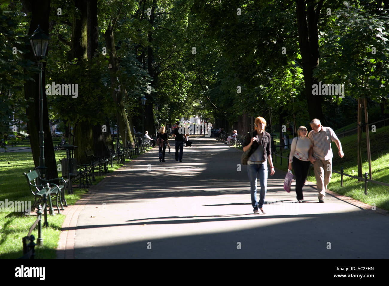 people walking along the footpath through the planty public parks in Krakow - Stock Image