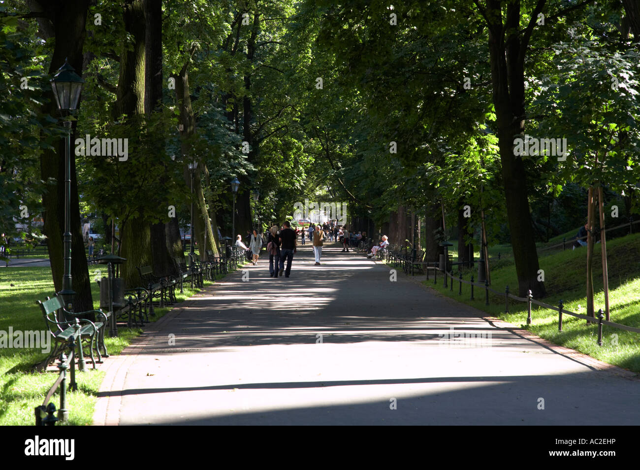 footpath through the planty public parks and gardens with people walking on them in Krakow - Stock Image