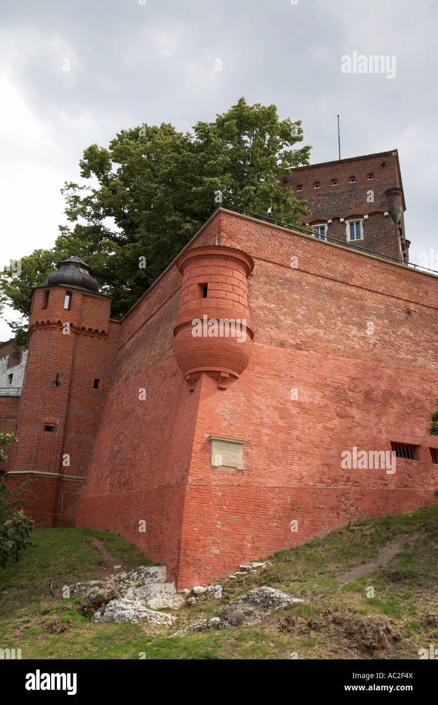 red brick high defensive walls and turret with tower down to dragons den wawel hill and castle krakow - Stock Image