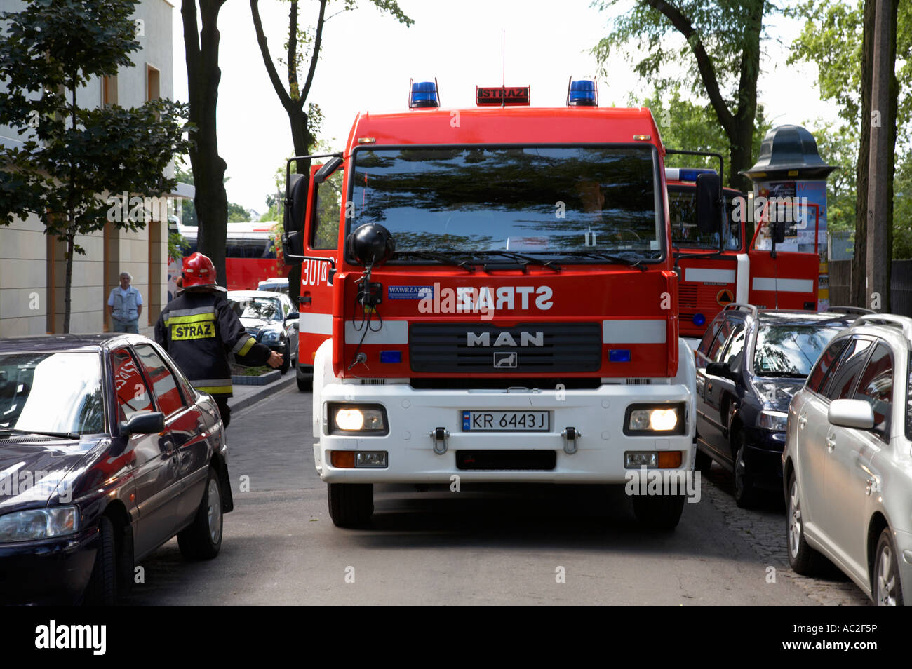 polish fire brigade fire guard straz krakow vehicle parked in middle of city street firefighter attending emergency - Stock Image