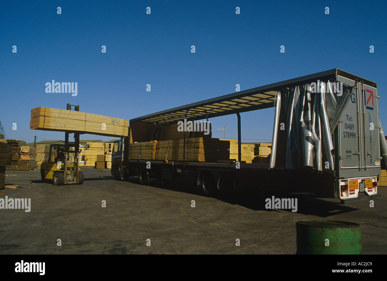 Cut timber from Scandinavia is landed stored and loaded onto trucks at Rowhedge near Colchester - Stock Image