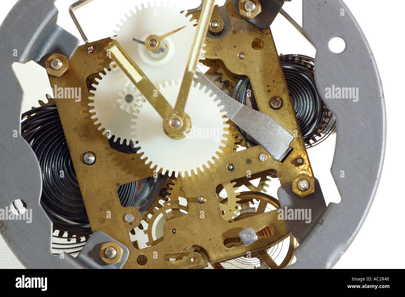 Inner working parts of an old windup clock on white background - Stock Image