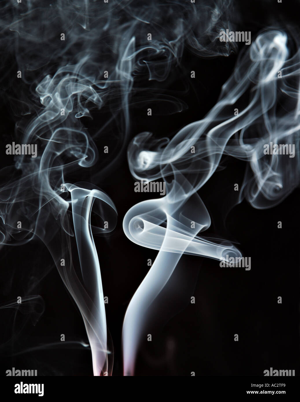 Curling smoke from two extinguished candles on black background - Stock Image