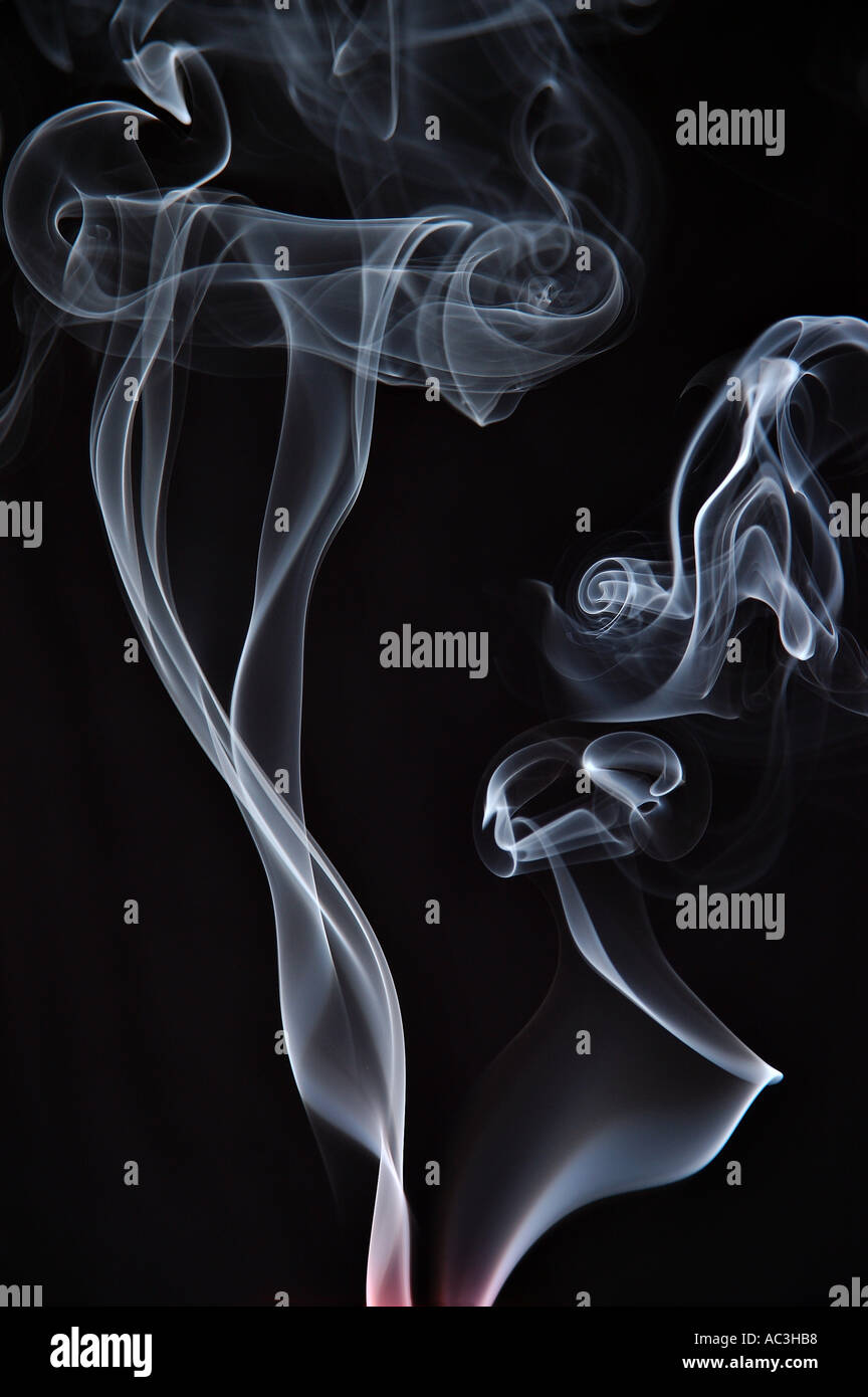 Shafts of curling smoke from extinguished candles or smoldering cigarettes - Stock Image