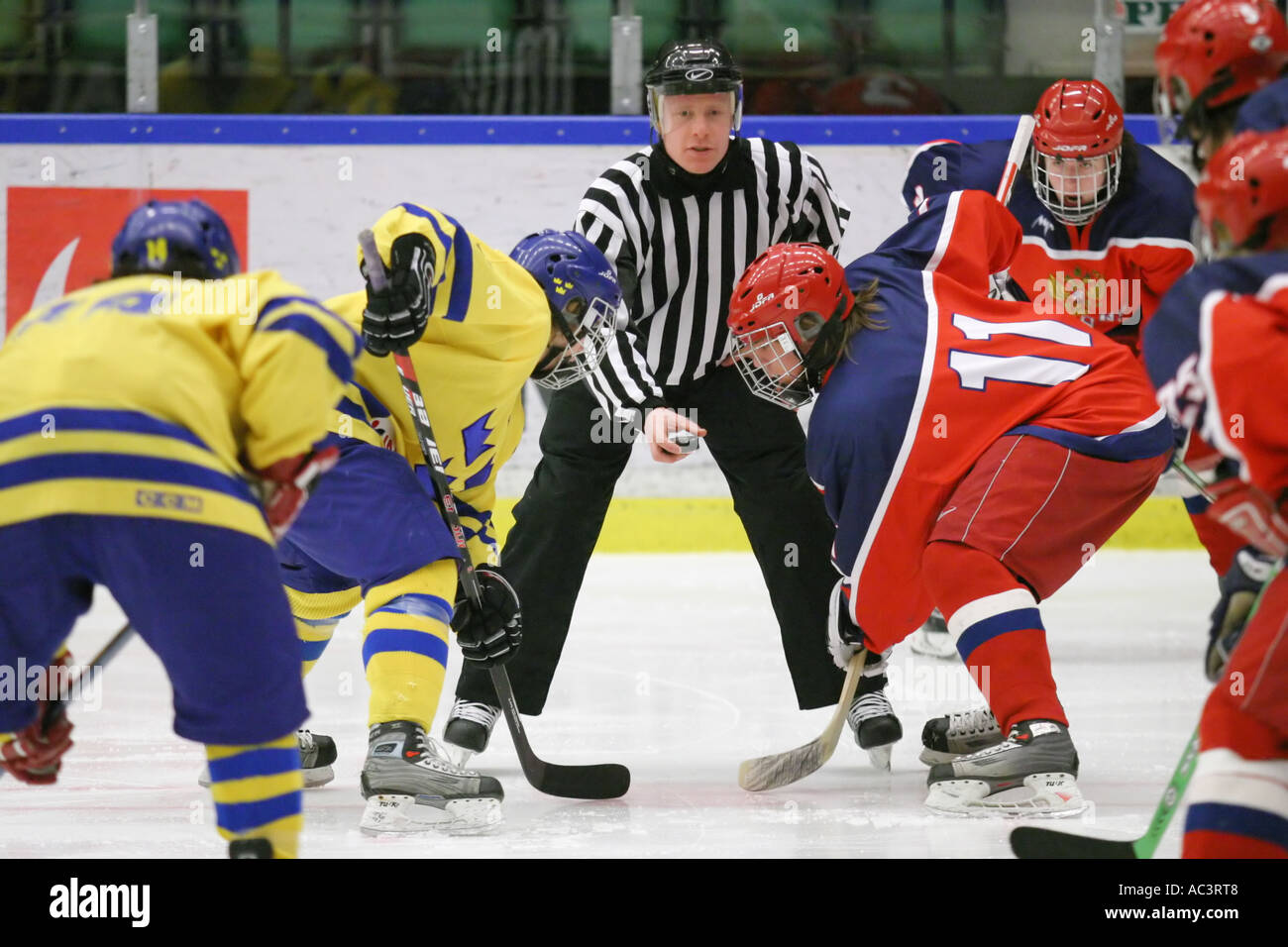 Face off at an ice hockey game between team Sweden and team Russia in an international tournament for 17 year old teenagers. - Stock Image