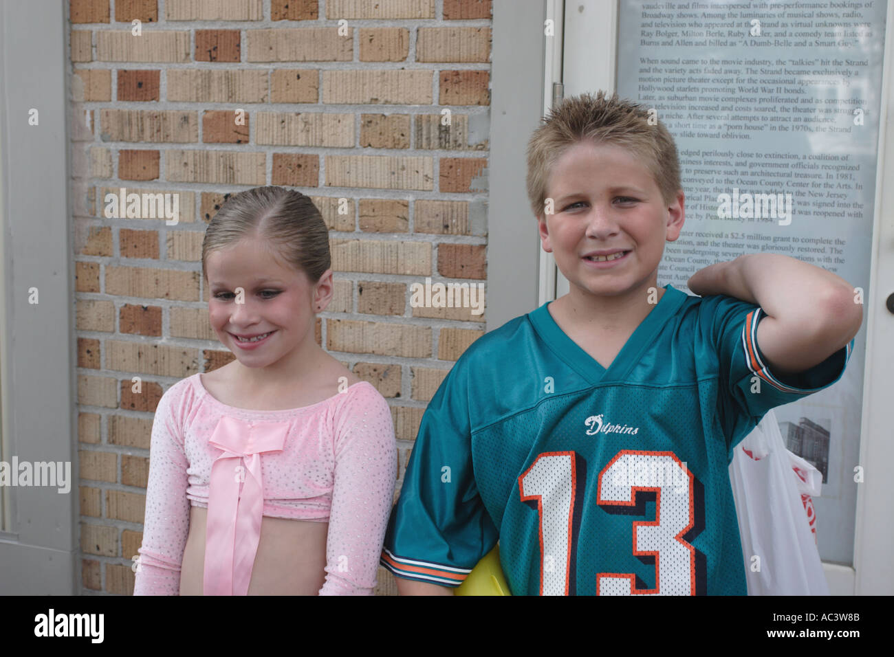 Young pretty girl poses after her dance recital with her football fan brother - Stock Image