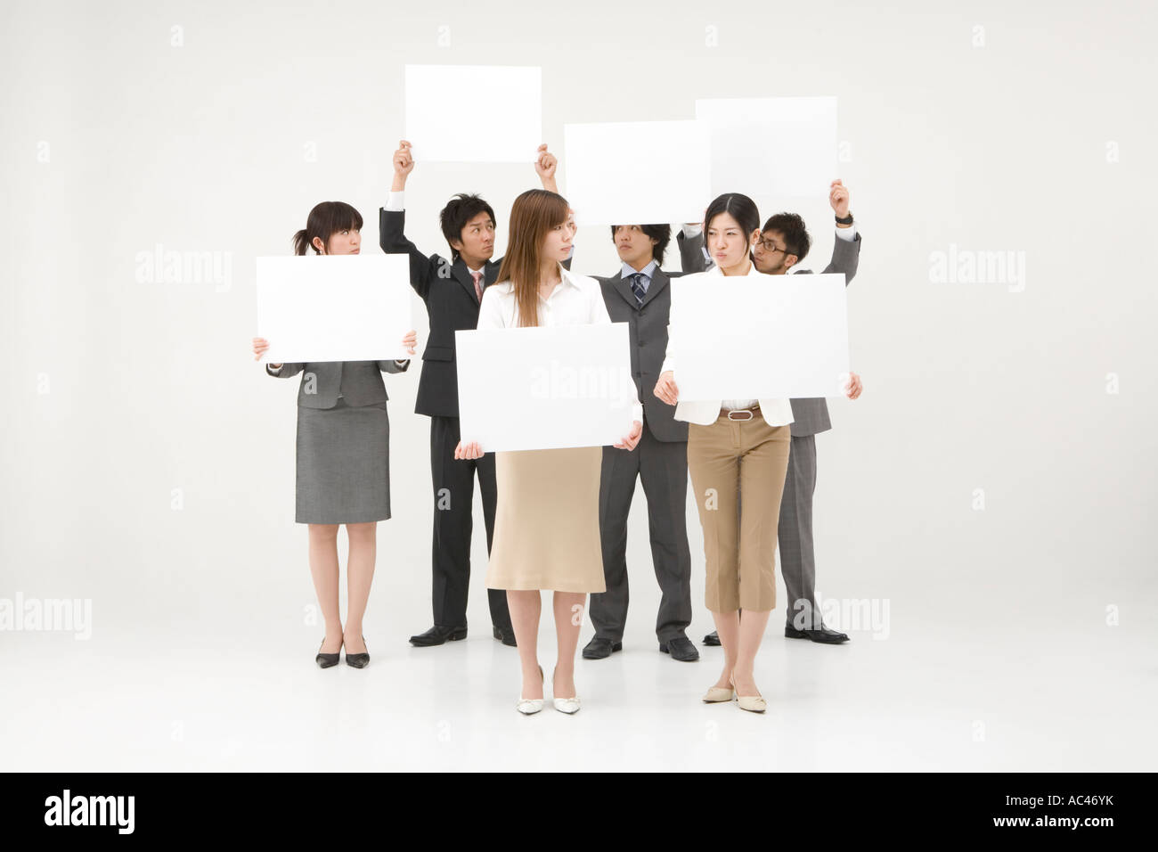 Business people holding blank placards - Stock Image