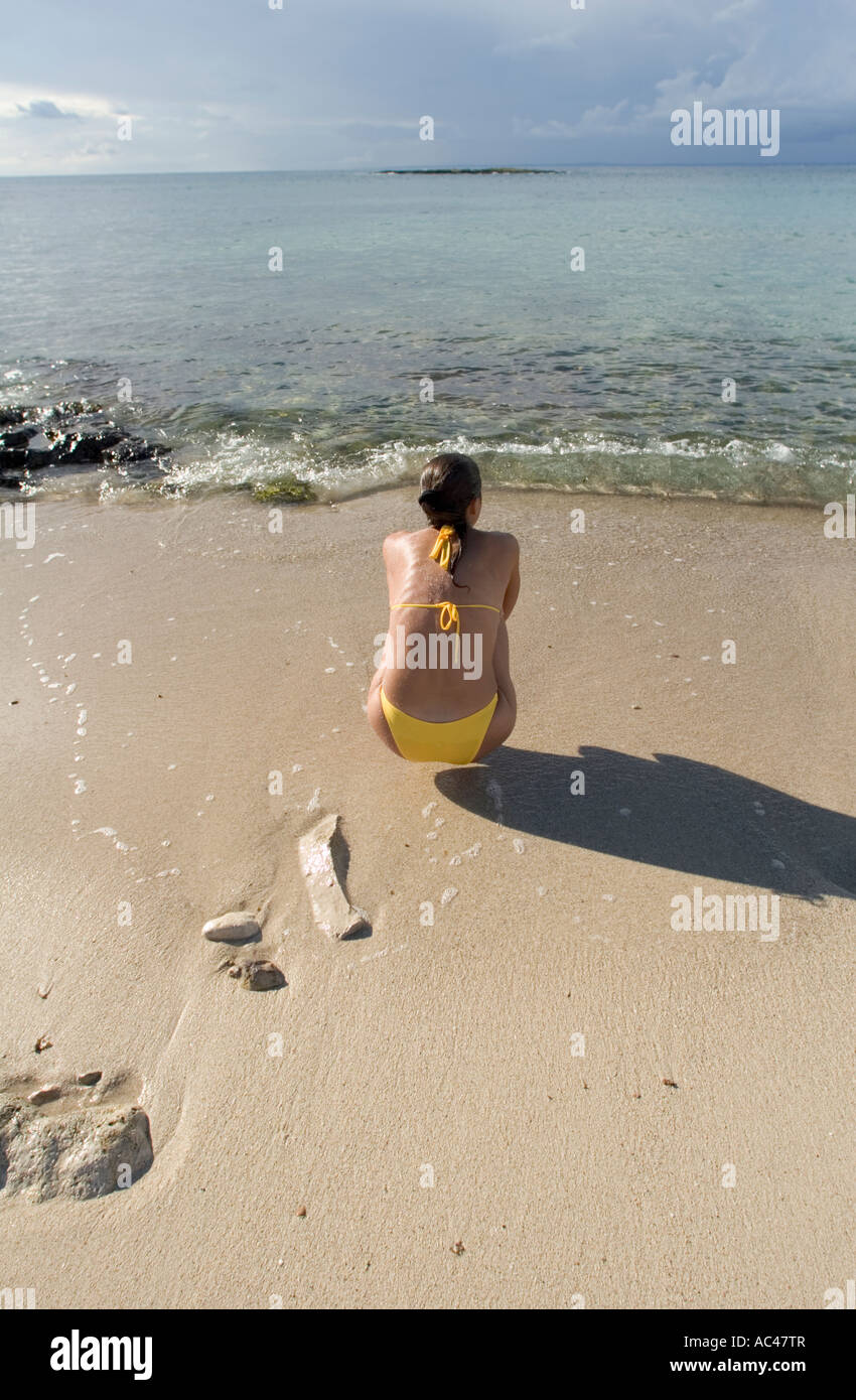 Young athletic woman in yellow bikini crouching on beach staring out to sea, Puglia, Italy - Stock Image
