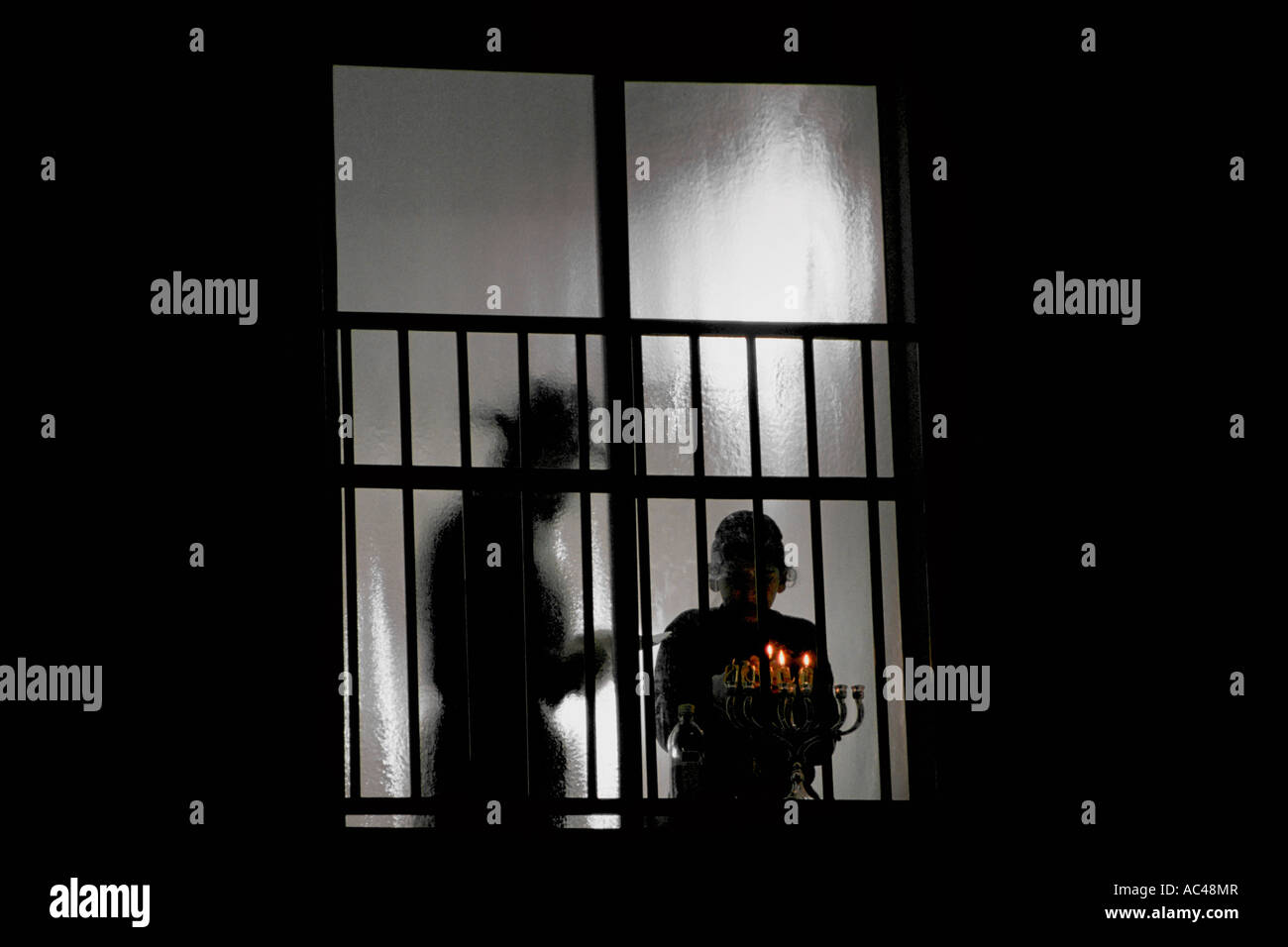 Israel. A Jewish Orthodox father and son, silhouetted through a window, light candles during the Jewish holiday - Stock Image