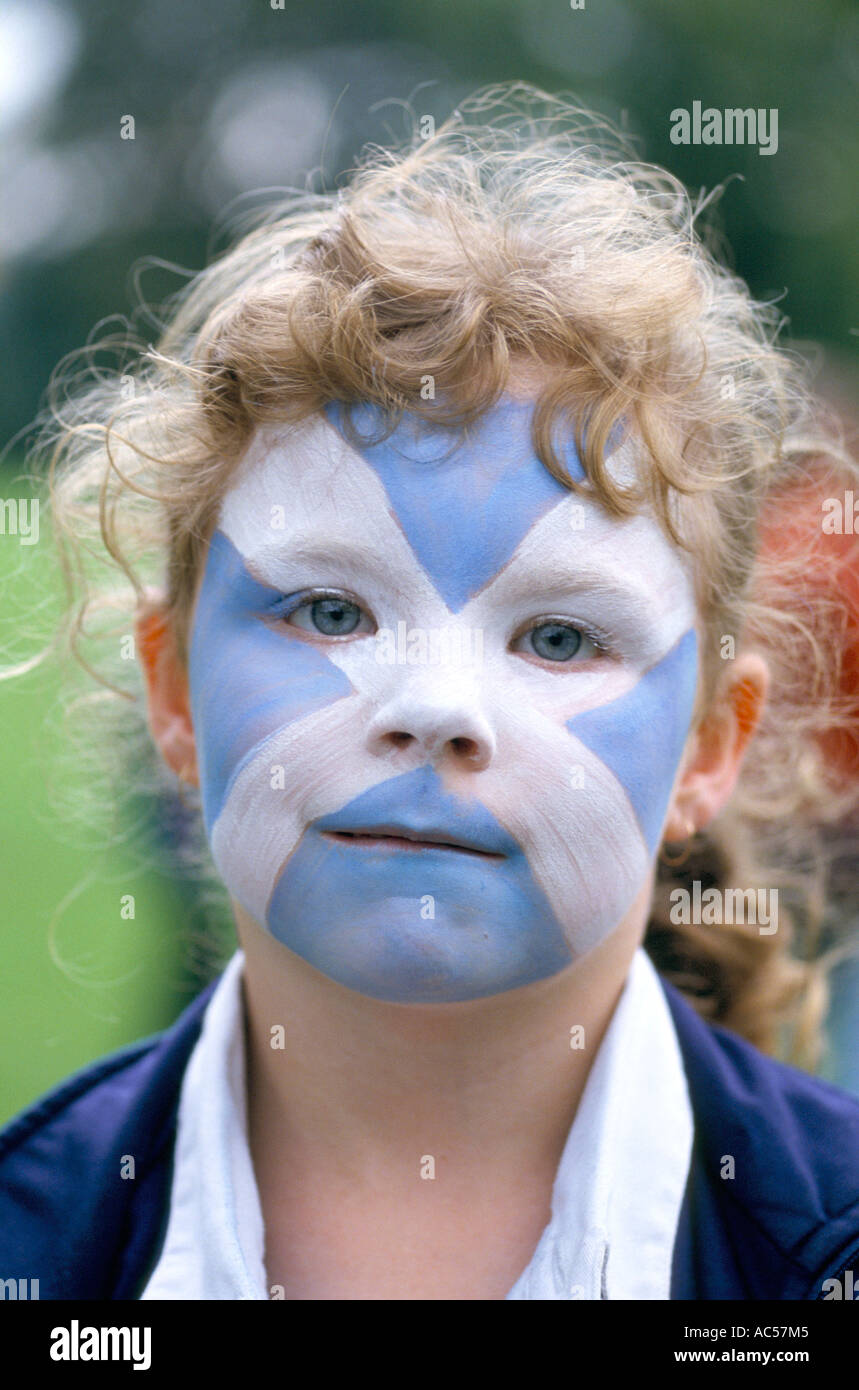SCOTTISH NATIONALISM YOUNG CHILD FACE PAINTED WITH CROSS OF ST ANDREW - Stock Image