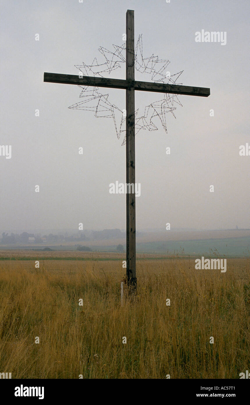 The fall of communism IRON CURTAIN  A CROSS ON THE BORDER NEAR HOF WHERE THE LAST FIGHTING OF WWII OCCURRED WREATHED IN BARBED W - Stock Image