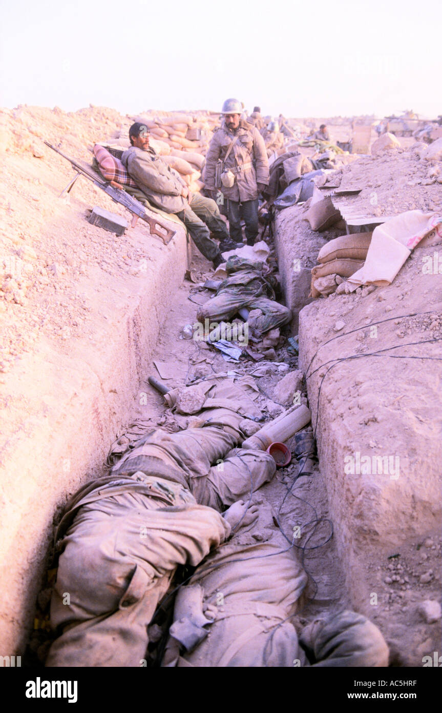 IRAQI TROOPS SURVEYING BODIES OF DEAD IRANIAN TROOPS IN  FRONTLINE TRENCH NORTH OF BASRA IRAQ 1984 - Stock Image