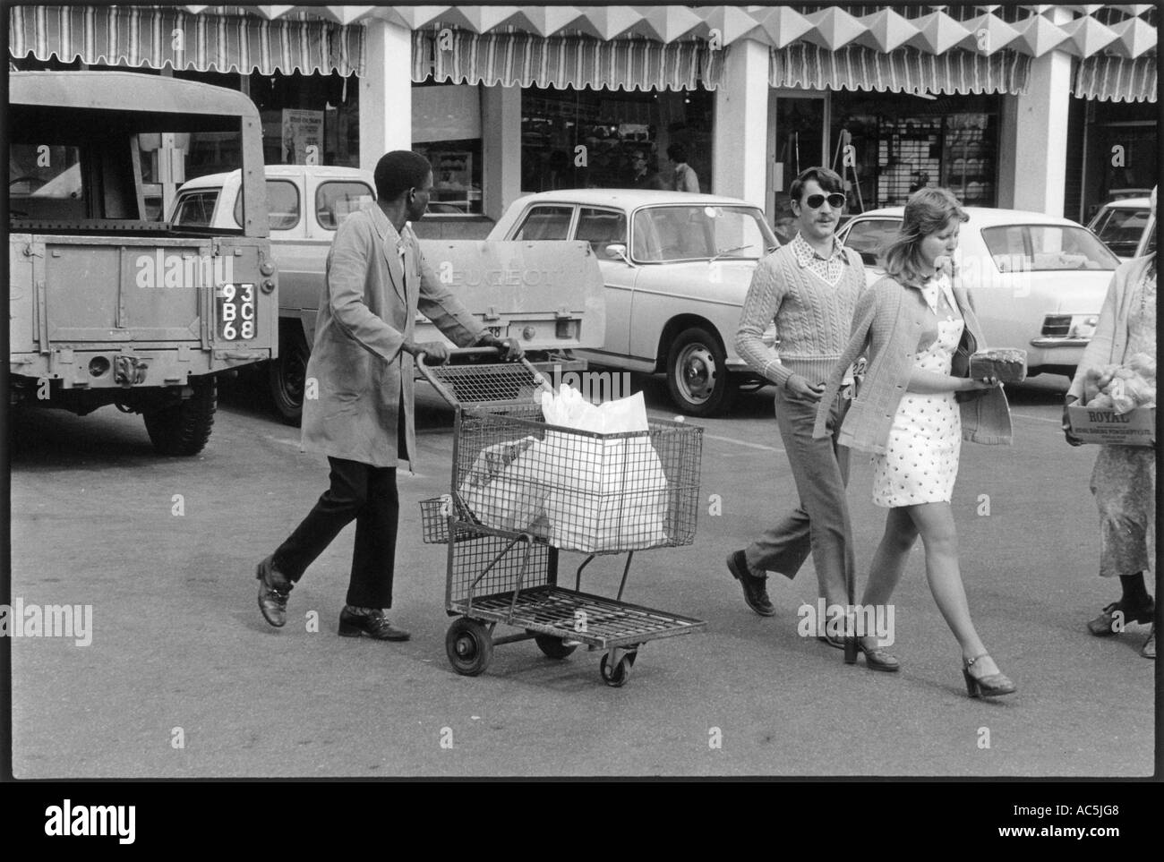 African man taking European couples' shopping to the car, Rhodesia 1975 - Stock Image