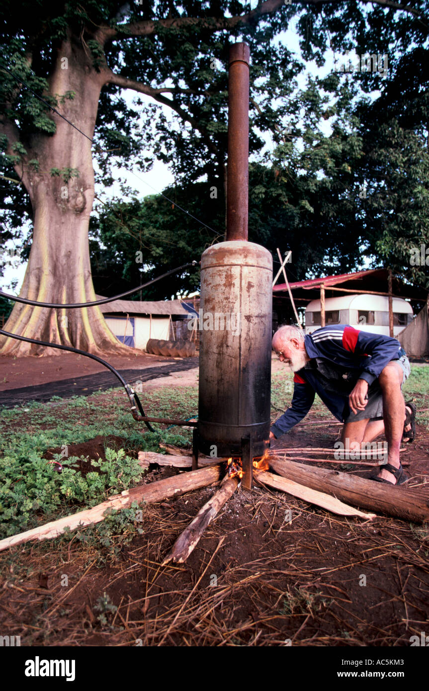 Former white Zimbabwean farmer lights a fire under his homemade boiler in Mozambique, May 2003