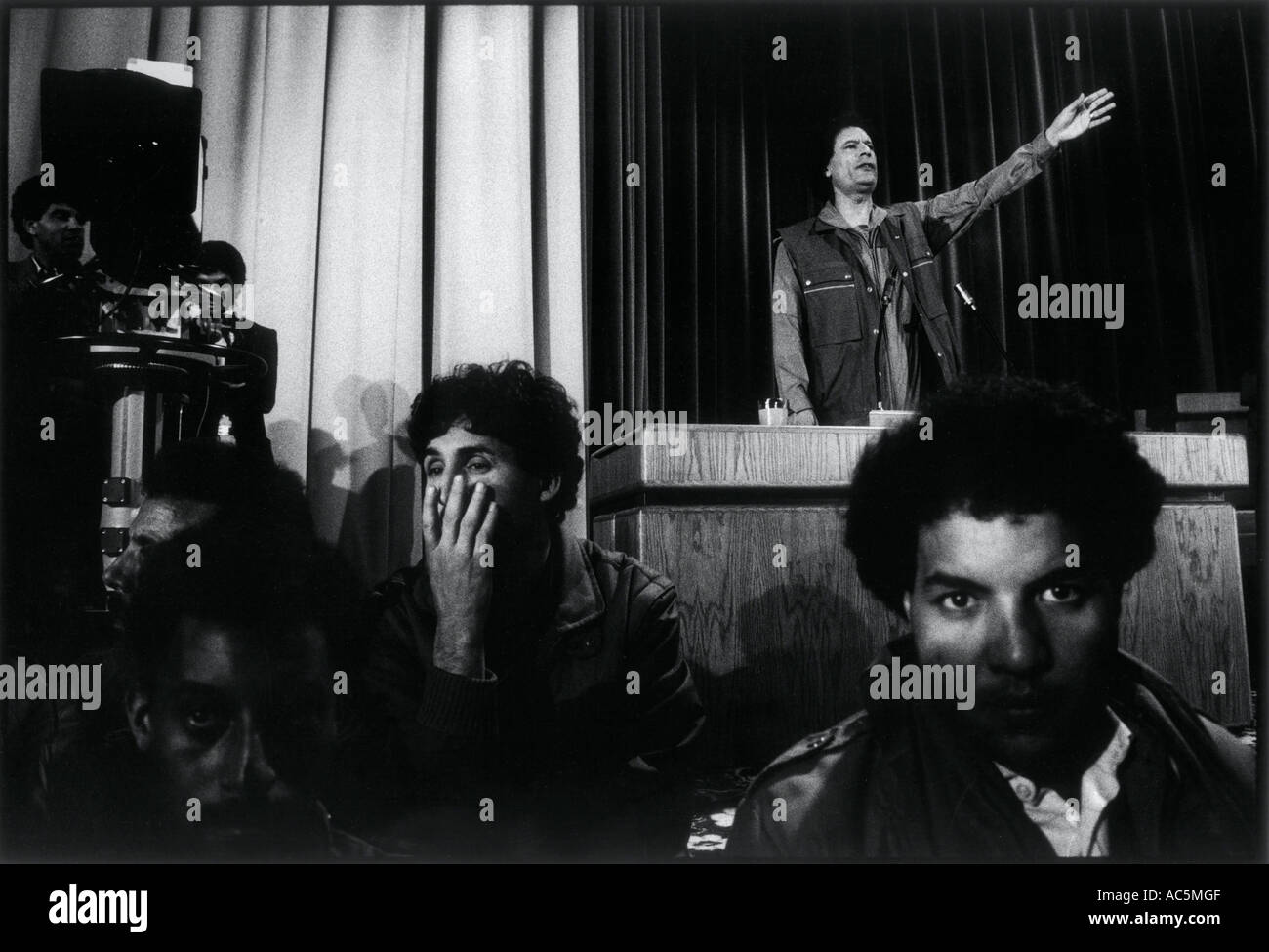 Muammar Gaddafi President of Libya at an indoor rally in Tripoli Security guards stand in front of him - Stock Image