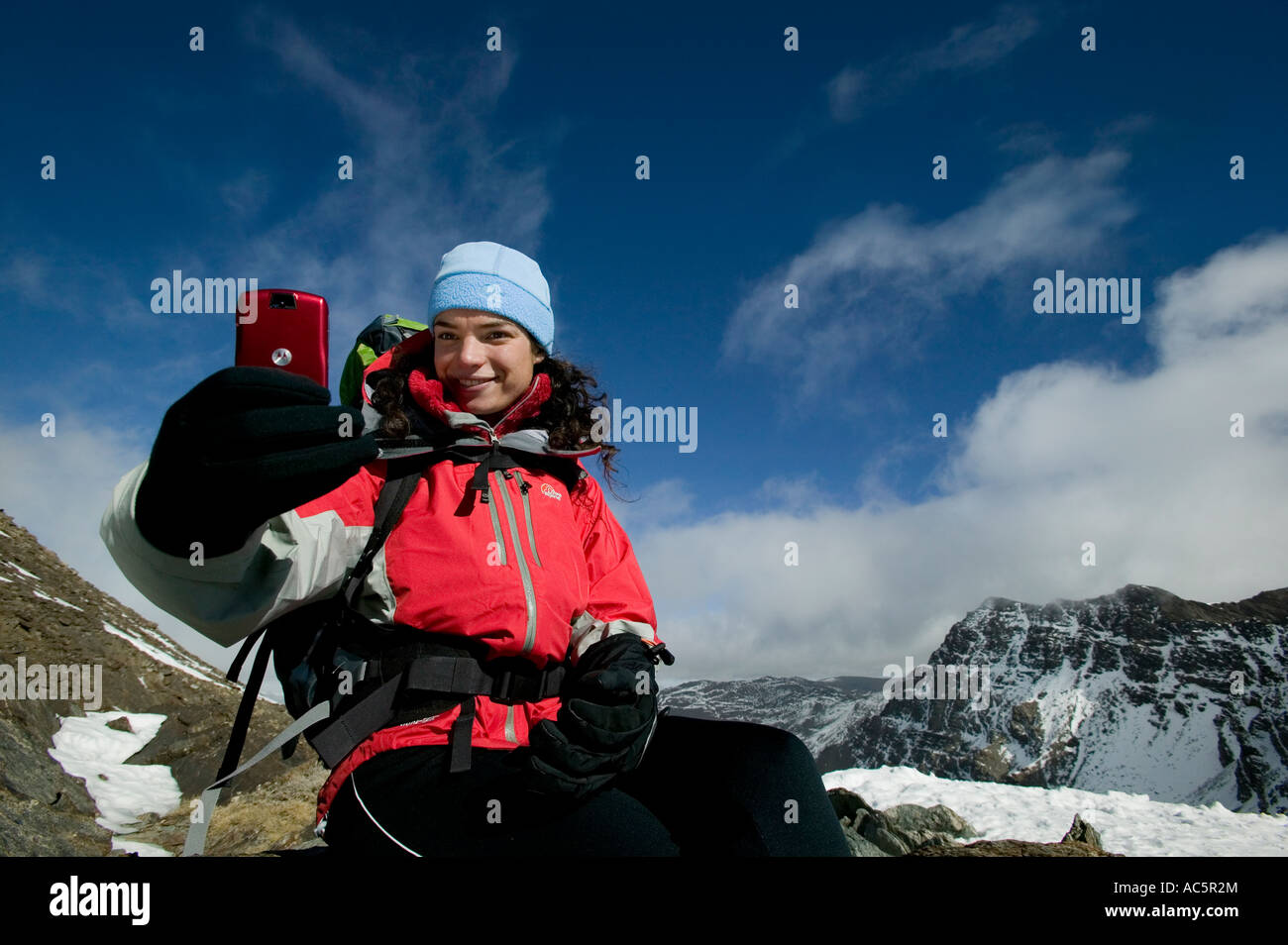 Woman taking a picture on a red camera phone in the mountains - Stock Image