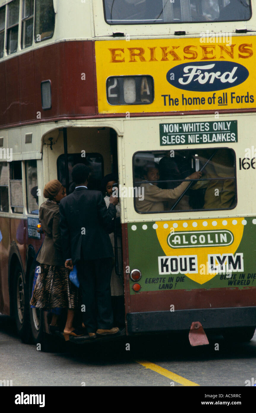PEOPLE CROWDING ONTO BUS WITH DISCRIMINATORY SIGN NON WHITES ONLY SLEGS NIE BLANKES AND ADVERTISMENT FOR FORD MOTORS - Stock Image