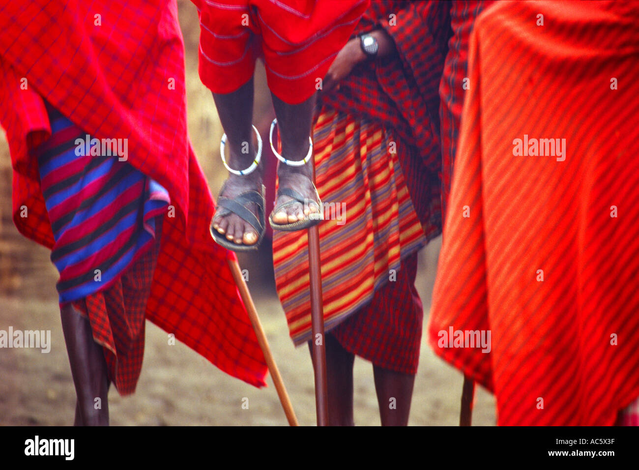 Masai tribesman performing ritual dance Serengetti Tanzania Masai tribesman Tanzania Red Robe Garb Tradition African Culture - Stock Image
