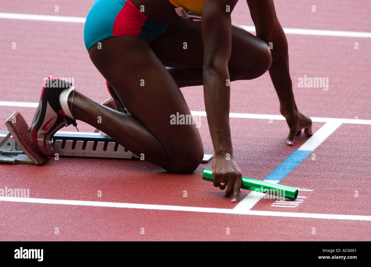 female competitior at a relay race lines upt her hands and baton with the starting line - Stock Image