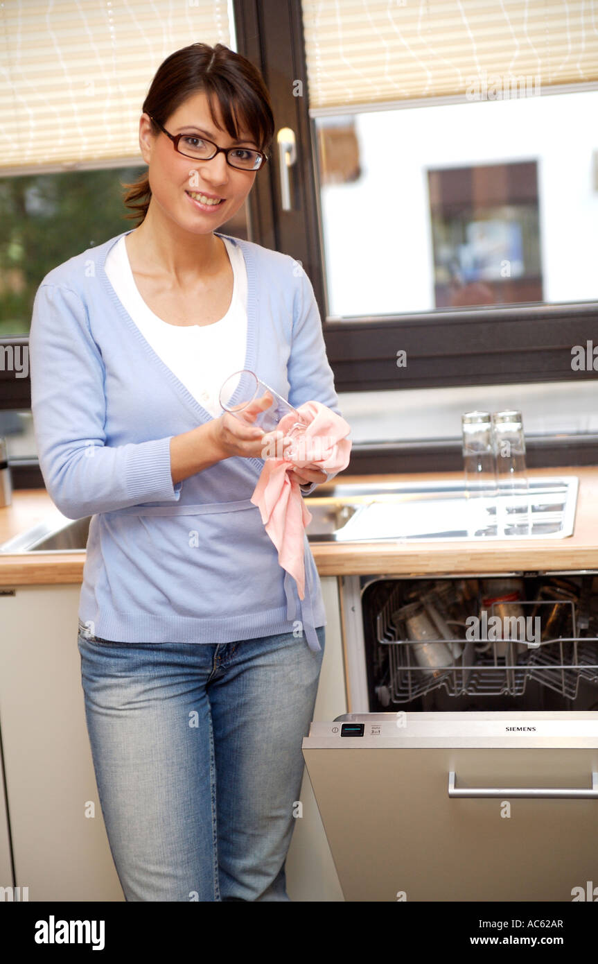 Junge Frau raeumt die Spuelmaschine aus young woman clearing out the dishwasher Stock Photo