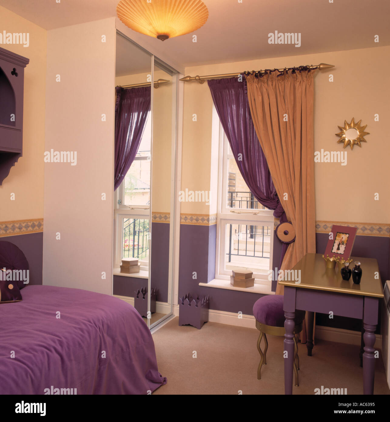 Purple And Gold Curtains At Window Beside Fitted Wardrobe With Mirrored Door In Apartment Bedroom Bedcover